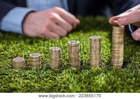 Close-up Of A Businessperson's Hand Stacking Coins On Green Grass