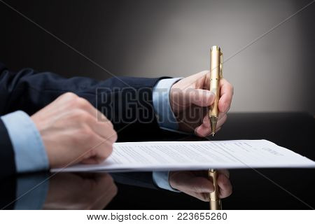 Close-up Of A Businessperson's Hand Holding Pen To Sign On Contract Paper
