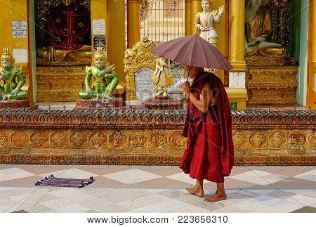 Yangon, Myanmar - Feb 26, 2016. A Monk Walking At Shwedagon Pagoda In Yangon, Myanmar. The Pagoda Is