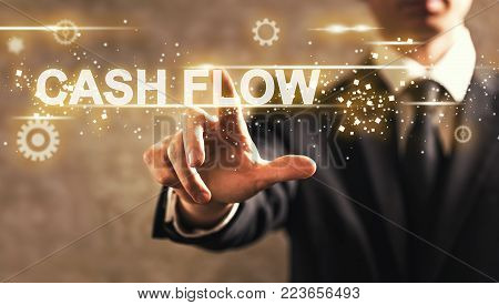 Cash Flow text with businessman on dark vintage background