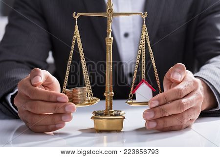 Close-up Of A Businessperson's Hand Protecting Stacked Coins And House Model On Weighing Scale