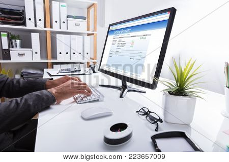 Close-up Of A Businessperson's Hand Doing Online Banking On Computer At Workplace