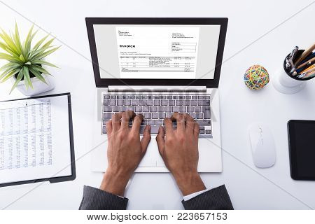 High Angle View Of A Businessperson's Hand Checking Invoice On Laptop In Office