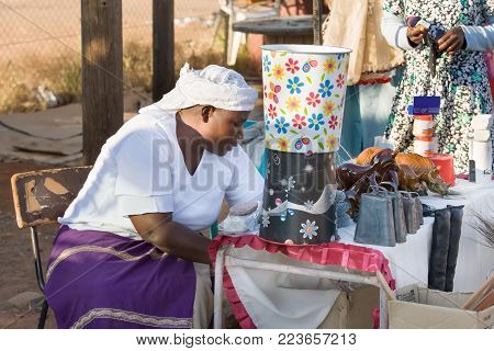 Zezuru African woman street vendor selling cow bells
