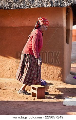 African senior woman standing in front of the house in the village, Botswana