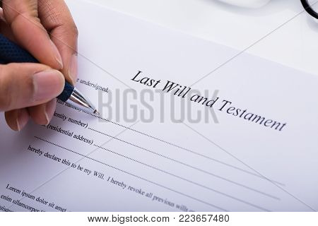 Close-up Of A Person's Hand Filling Last Will And Testament Form