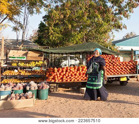 African woman street vendor with oranges and bananas