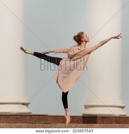 Slender young ballerina in pointe dancing in the street. Performance. The art of dance. Slender female feet. Classical ballet.
