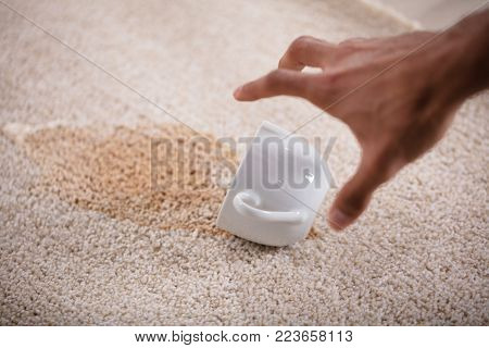 Close-up Of A Person Picking Cup With Spilled Coffee On Carpet