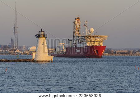 New Bedford, Massachusetts, USA - January 19, 2018: Geotechnical drill ship Fugro Explorer passing Palmer's Island lighthouse during early morning departure from New Bedford