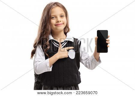 Little schoolgirl holding a phone and pointing isolated on white background