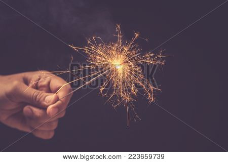 Christmas And New Year Celebration Concept : Hand Holding Bright Burning Christmas Sparkle On Black
