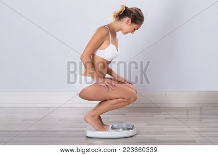 Woman Measuring Her Weight On Weight Scale At home