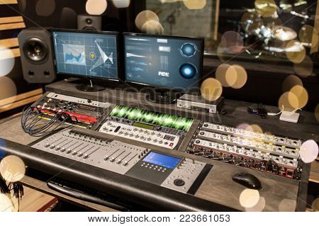 music, technology, electronics and equipment concept - mixing console and computer monitors at sound recording studio over lights