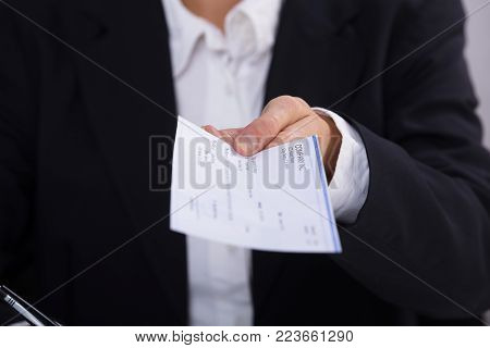Close-up Of A Businessperson's Hand Holding Cheque In Office