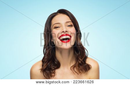 beauty, make up and people concept - happy laughing young woman with red lipstick over blue background