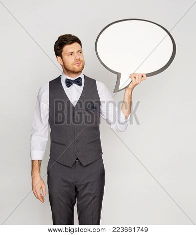 fashion, style and communication concept - concerned man in suit holding blank text bubble banner