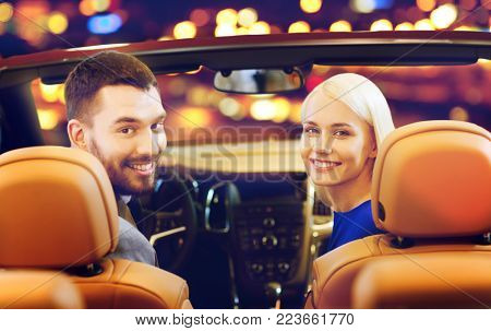 vehicle, luxury and people concept - happy couple driving in convertible car over night city lights background