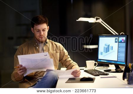 design, deadline and technology concept - graphic designer with papers and computer working at night office