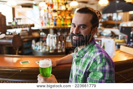 people, leisure and st patricks day concept - happy man drinking green beer at bar or pub