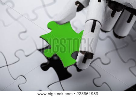 Close-up Of A Robot's Hand Holding Green Jigsaw Puzzle