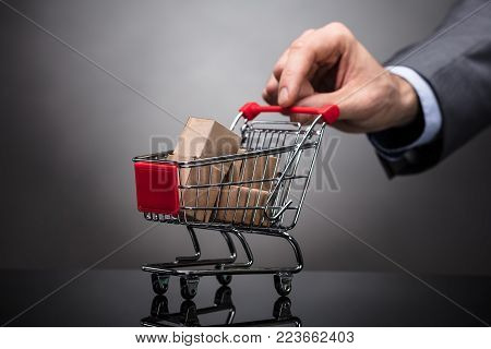 Businessperson's Hand Holding Shopping Cart With Cardboard Boxes On Grey Background