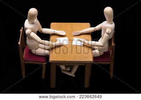 Elevated View Of Two Wooden Dummy Figures Discussing Business Document At Workplace