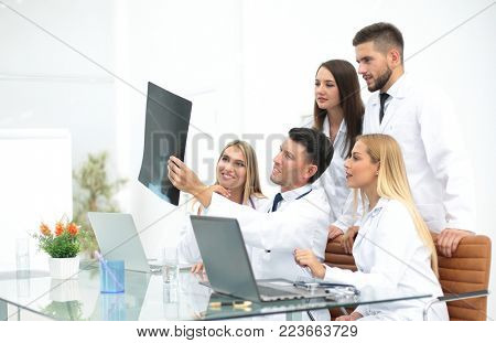 group of doctors discussing an x-ray ,sitting at the table.