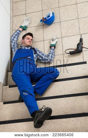 Unconscious Handyman Lying On Staircase With Helmet And Drill On Floor