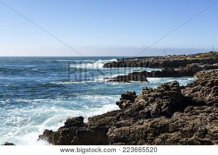 Rocky and steep rugged coastline near Cascais, Portugal