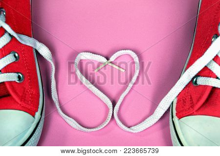 pair of bright red sneakers with shoestring heart on pink background