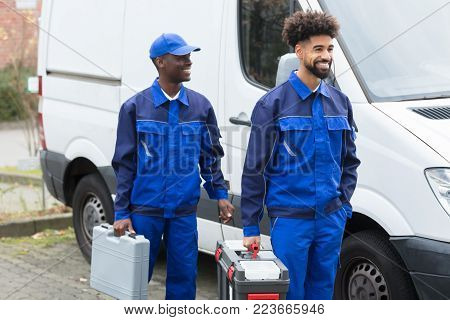 Portrait Of Two Smiling Manual Workers With Their Tool Boxes Standing Near The White Van