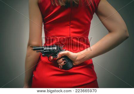 Armed girl in a red dress hides her pistol gun behind her back. Hidden threat. Killer woman.
