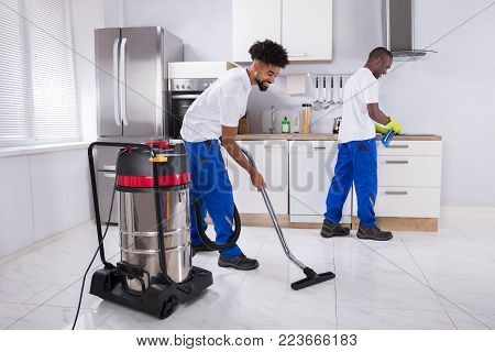 Two Young Male Janitor In Uniform Cleaning The Induction Stove And Floor In The Kitchen