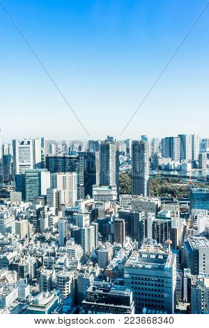 Asia Business concept for real estate and corporate construction - panoramic modern city skyline bird eye aerial view with crane near tokyo tower under bright sun and vivid blue sky in Tokyo, Japan