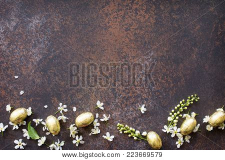 Easter Concept. Colorful Easter Background With Chocolate Eggs And Blooming Bird Cherry On A Stone O