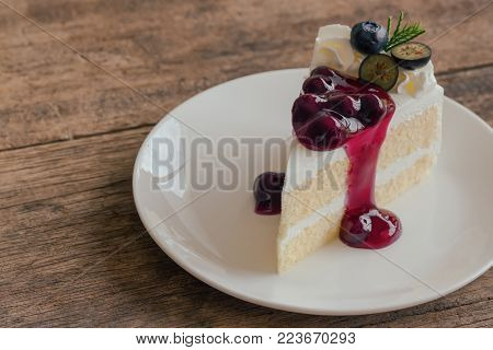 Blueberry cream cake on white plate on wood table with copy space. Vanilla blueberry sponge cake decorated with dairy whipped cream and blueberry sauce so soft sweet and delicious. Homemade bakery background. Blueberry cake ready to serve.