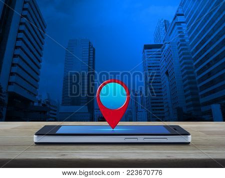 Map pin location button on modern smart phone screen on wooden table over office city tower, Map pointer navigation concept