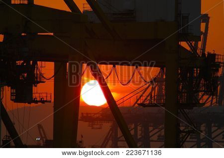 The rising sun is a white ball against an orange sky. It is silhouetted against the black of industrial machinery.