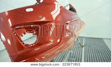 Car bumper after painting in a cars spray booth. Auto vehicle cherry color bumper. Parts of car in cars spray booth.