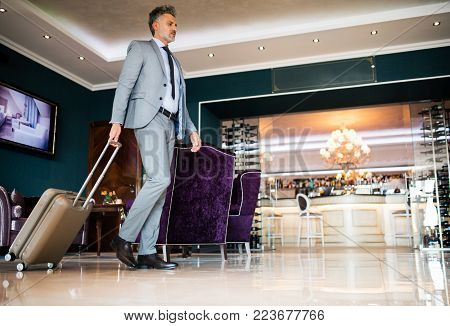 Mature businessman entering or leaving hotel with luggage. Man walking in the hotel entrance hall.