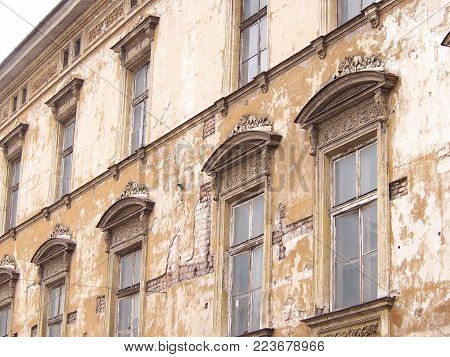 An old uninhabited tenement house in the old town of Krakow. Beautiful windows and destroyed façade.