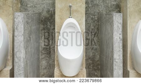 White urinal men with concrete wall loft style for interior design or exterior design. White urinal men in public toilet. Chamber pot or urinal   men classic and retro style center position