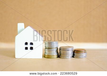 A house model with a row coins on blur wooden background for saving money and purchase a house idea