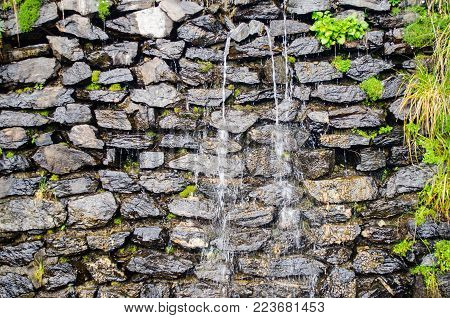 Small Waterfall On The Small Brick Wall