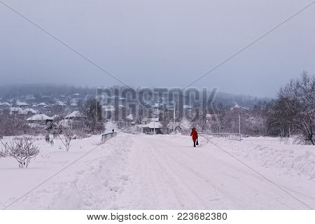Photo winter morning early in the morning when the sun is very low. A rural snowy landscape with a road and a walking man in red.