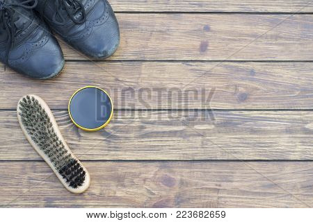 old shabby black shoes sleep laces. shoe polish and a new shoe brush. on a wooden background. view from above