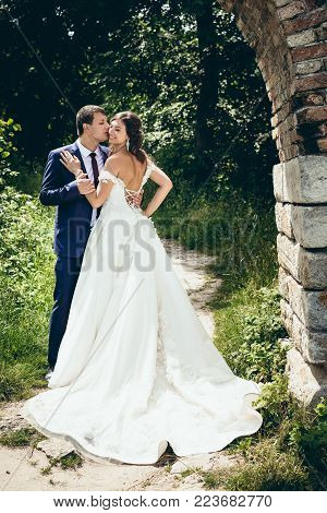 Full-length wedding portrait of the groom tenderly kissing his lovely bride with open back in cheek in the green forest. Look through the stone arch