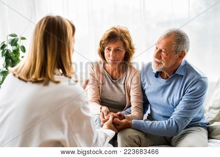 Young female doctor talking to a senior couple.