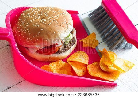 Sweeping junk food with burger chips and dustpan concept of health detox diet